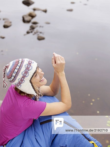 Woman with sleeping bag wrapped around her waist smiling by water.