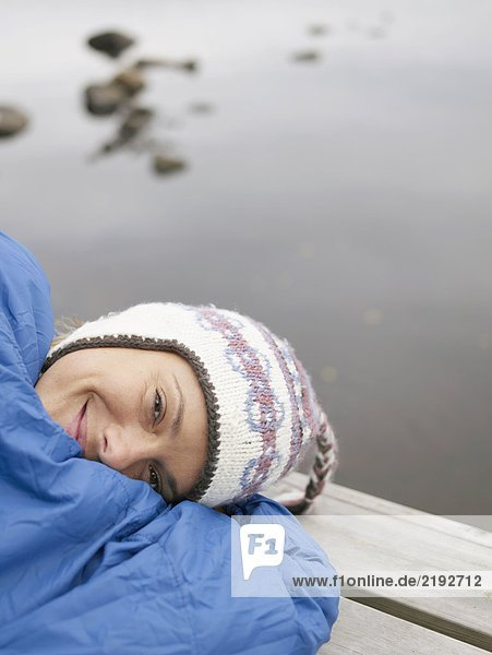 Woman with on a dock in a sleeping bag smiling.