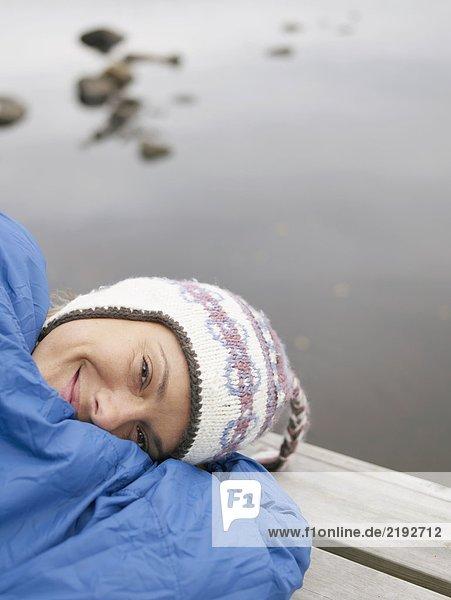 Frau mit auf einem Dock im Schlafsack lächelnd.
