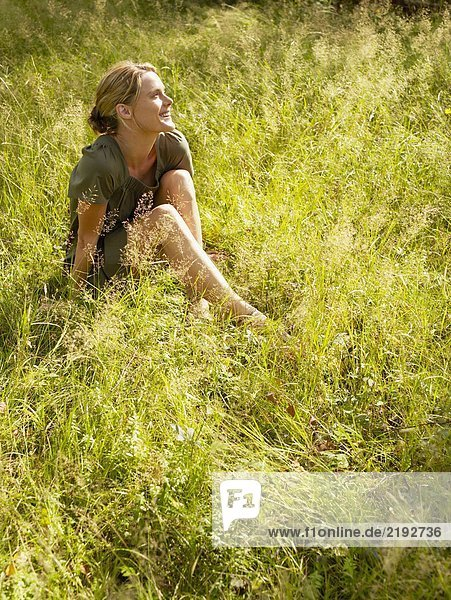 Woman sitting in the grass smiling.