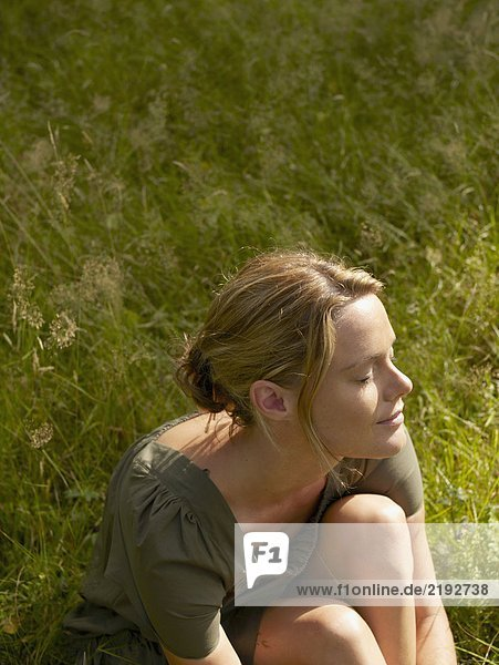 Woman sitting in the grass with eyes closed.
