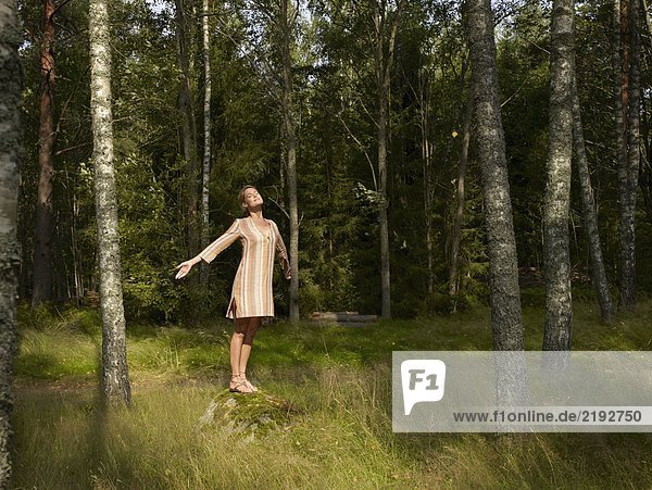 Woman standing on a large rock in forest.