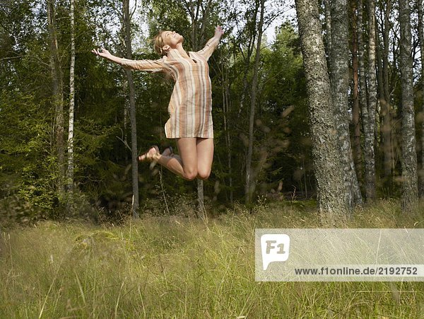 Woman jumping in a forest smiling.