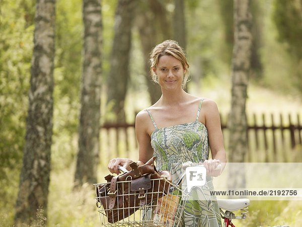 Woman standing with bike by wooden fence.
