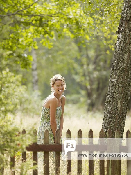 Woman standing by wooden fence laughing.