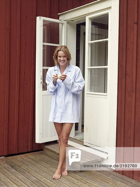 Woman standing outside doorway with mug smiling.