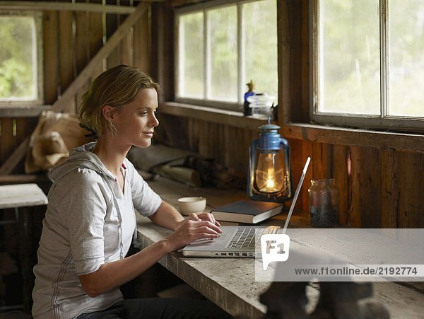 Woman with laptop and mug sitting at table in cabin.