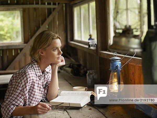 Frau sitzt an einem Tisch in der Kabine mit Buch und Brille.