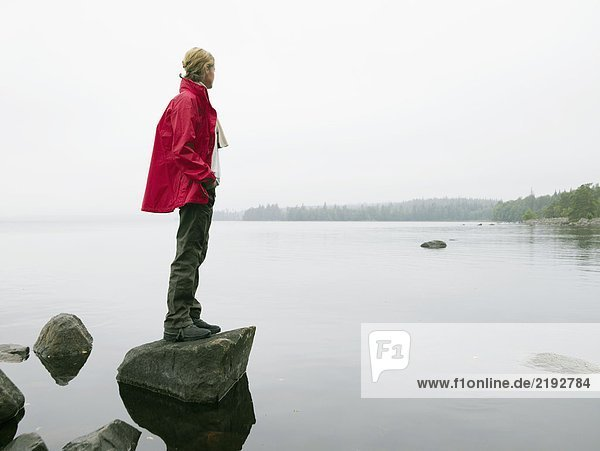 Woman standing on large rock in the water.