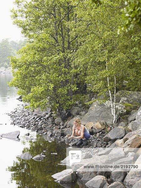 Woman washing her hands in a lake.