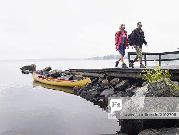 Couple walking on dock near a boat.