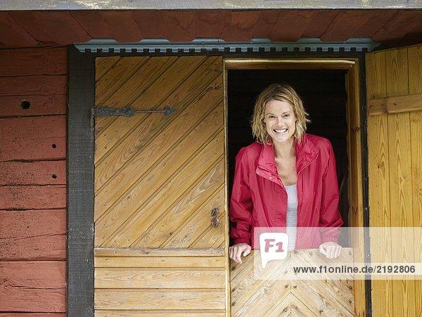 Woman standing in a doorway smiling.