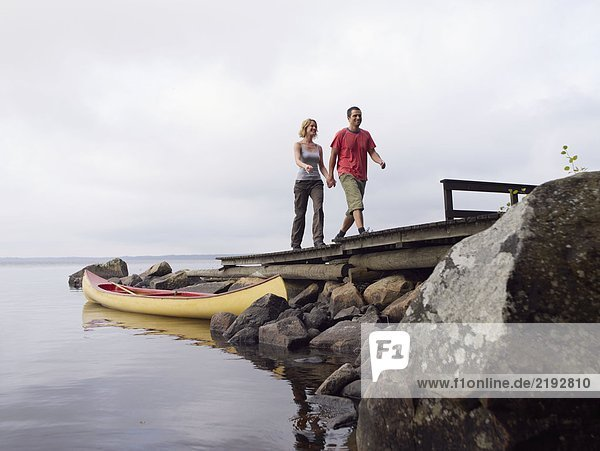 Couple holding hands walking on a dock near a boat smiling.