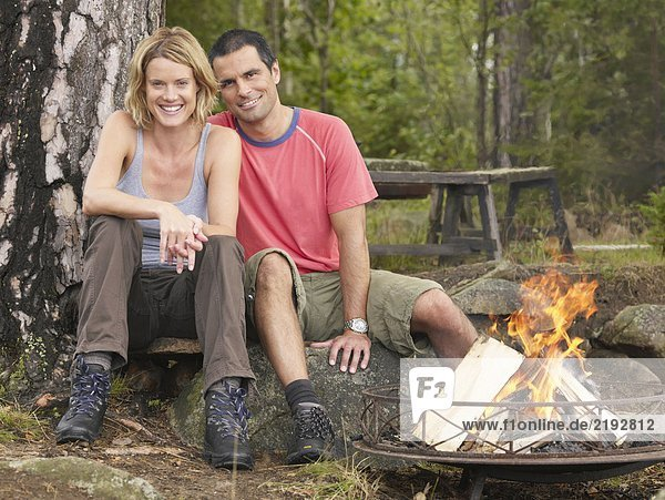 Couple sitting by a fire pit smiling.