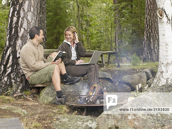 Woman with laptop and man with book near a fire pit smiling.