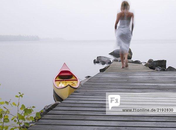 Eine Frau  die auf einem Dock in der Nähe eines Bootes läuft.