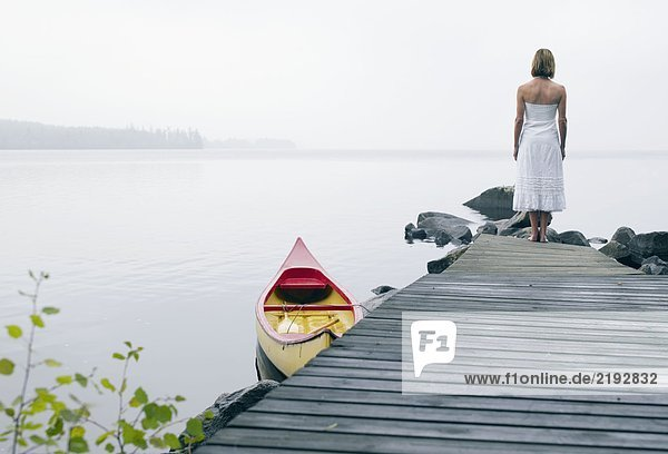 Woman standing on a dock near a boat.