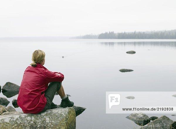 Woman sitting on large rocks by a lake.
