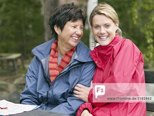 Two women sitting at a table with a map smiling.