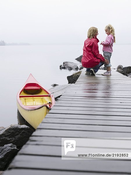 Woman with young girl standing on a dock smiling.