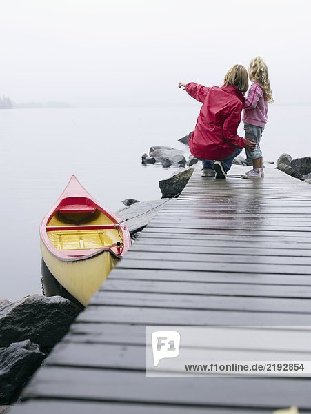 Woman and young girl on a dock near a boat pointing.