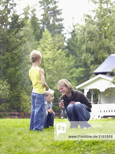 Woman with young girl and young boy in yard picking flower smiling.