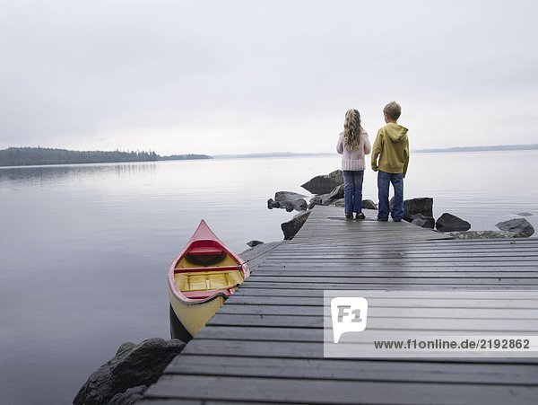 Young girl and young boy standing on a dock near a boat.