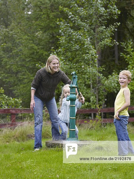 Woman with young boy and young girl using outdoors water pump smiling.