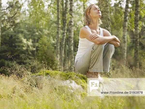 Frau kauert auf einem großen Felsen im Wald mit geschlossenen Augen.