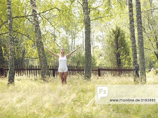 Woman standing by a wooden fence with arms outstretched.