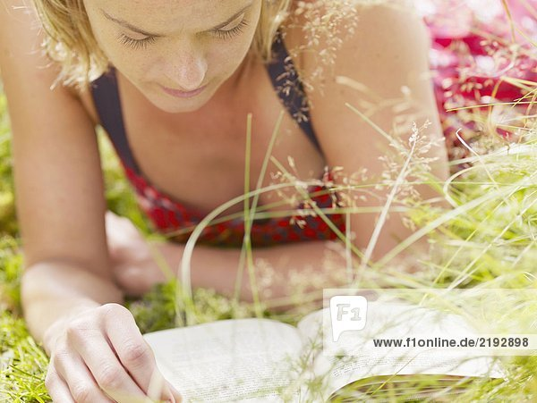 Woman lying in grass reading a book.