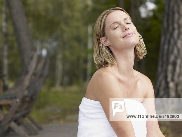 Woman wearing towel with eyes closed outdoors smiling.