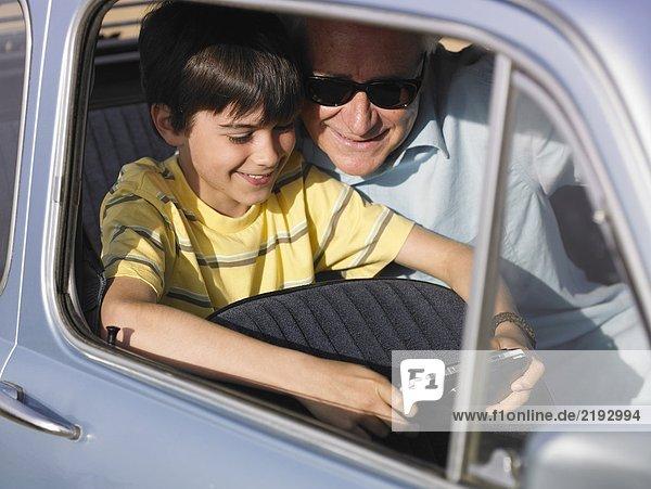 Junge (8-10) und Großvater spielen ein tragbares Videospiel auf dem Rücksitz des Autos.