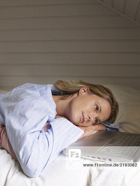 Geschäftsfrau  die sich mit der Arbeit auf dem Bett ausruht.