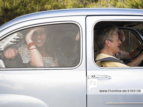 Mehrgenerationen-Familie im Auto sitzend  Seitenansicht  lächelnd