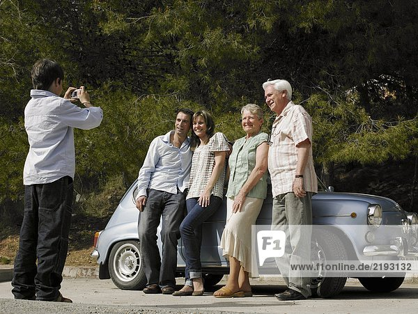 Multi-generational family standing beside car  boy (8-10) taking photo