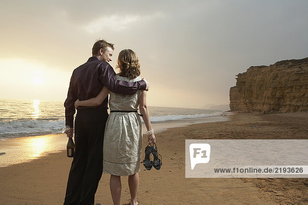 Couple walking together on beach.