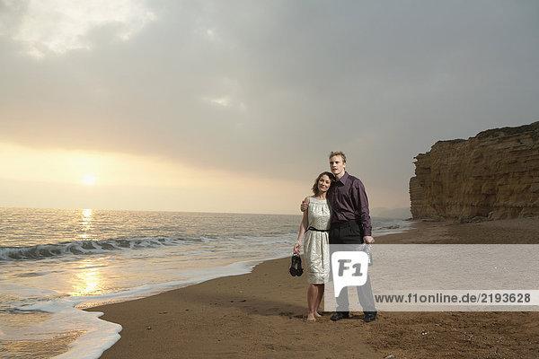 Ein Paar steht bei Sonnenuntergang am Strand.