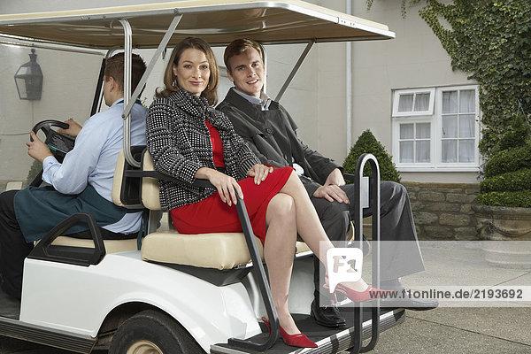 Mann fährt Wagen mit Mann und Frau.