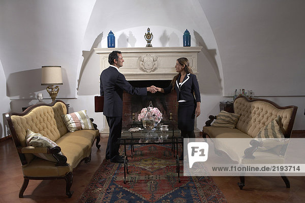 Businessman shaking hands with woman in living room