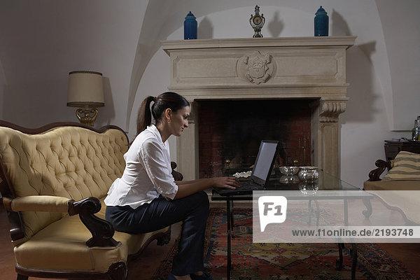 Frau auf dem Sofa sitzend mit Laptop