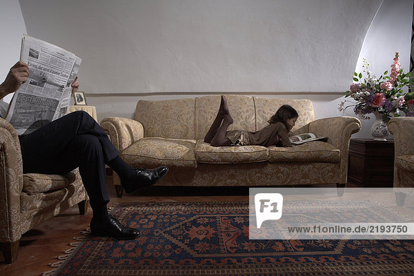 Man reading newspaper with daughter (5-7) reading book on sofa