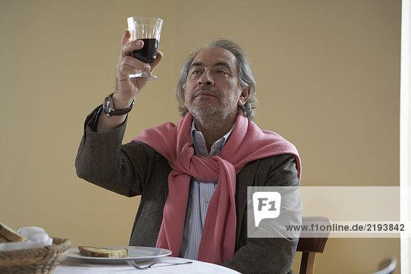 Senior man looking at wine at table