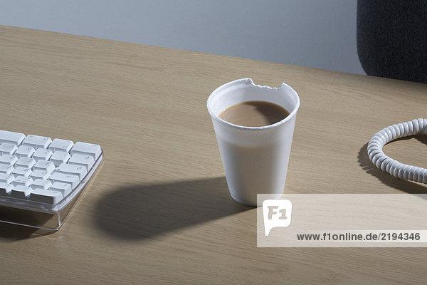 Eine Styropor-Tasse Tee mit einem Stückchen davon.