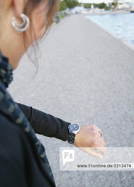 Frau schaut auf ihre Uhr