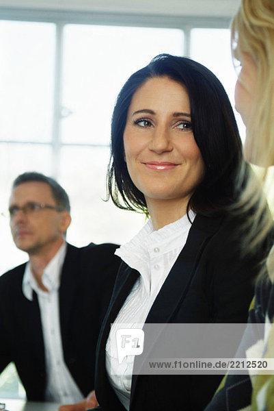 Geschäftsfrau hört einem Kollegen zu