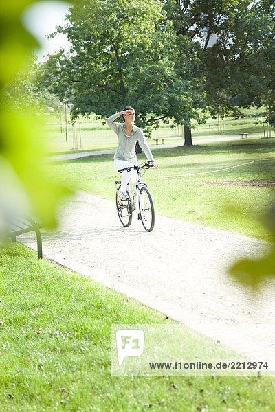 Junge Frau Fahrradfahren im park