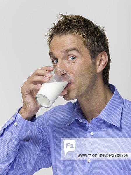 Junger Mann trinkt ein Glas Milch  Porträt