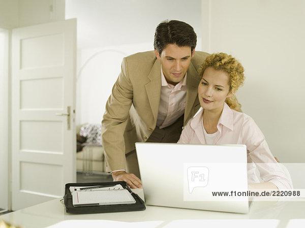 Junger Mann beobachtet  Frau benutzt Laptop