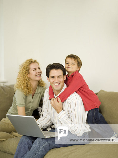 Young family in living room  father using laptop